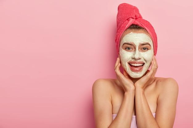 행복한 젊은 유럽 여성의 수평 샷은 얼굴 진흙 마스크를 적용하고, 뺨을 만지고, 피부 자극을 피하고, 벌거 벗은 어깨를 가지고 있습니다.