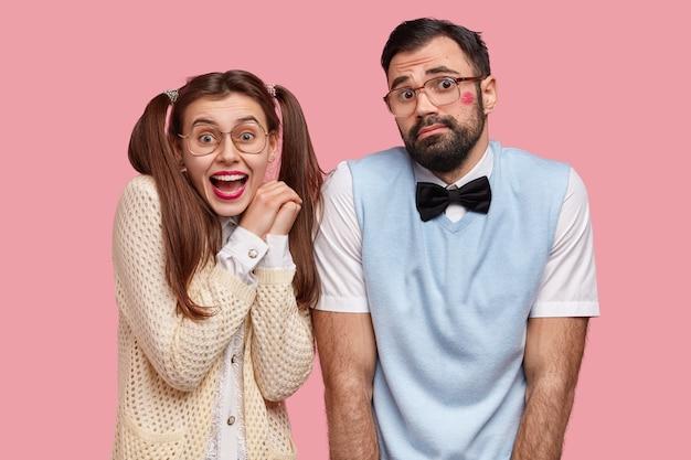 행복하고 주저하는 표정으로 행복한 젊은 유럽 여자와 남자의 가로 샷, 첫 데이트가 있고, 행동하는 법을 몰라, 분홍색 벽 위에 고립 된 오래된 유행의 옷을 입는다.