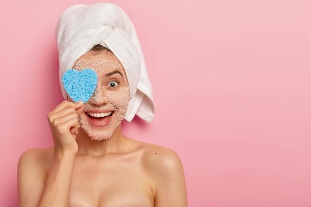 행복한 젊은 여성 모델의 가로 샷은 화장품 스폰지로 눈을 덮고, 천연 백해 소금 스크럽 마스크로 얼굴을 청소하고, 스파 살롱을 방문하고, 건강한 피부, 알몸, 실내 모델을 진정시킵니다.