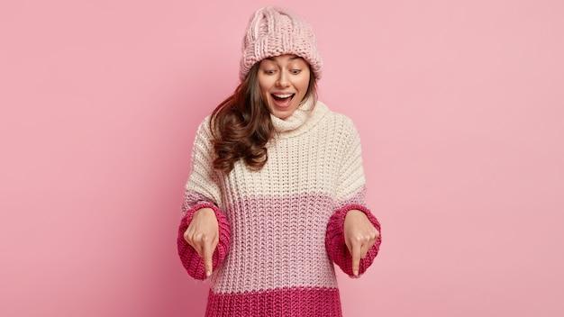 喜んでいる表情で幸せな若い女性の水平方向のショット、嬉しそうに笑う、前指で下向き、エキサイティングな何かを示し、ファッショナブルな暖かい服を着て、屋内でポーズをとる。