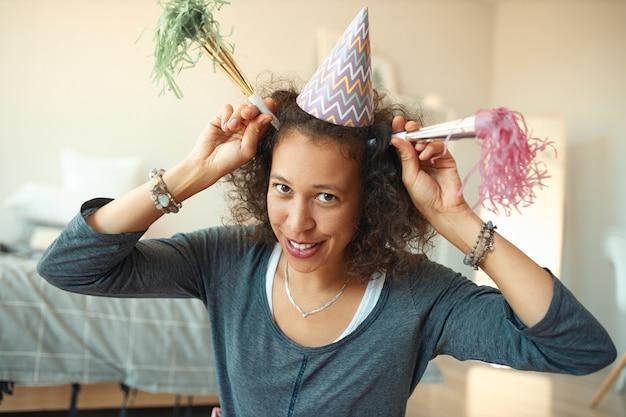 Горизонтальный снимок счастливой молодой женщины смешанной расы в конической шляпе на голове, веселящейся и дурачащейся