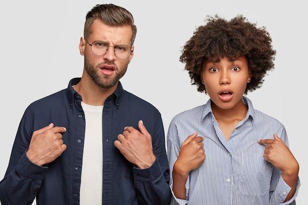 憤慨している若い女性と異なる人種の男性の水平方向のショットは、自分自身を指しています