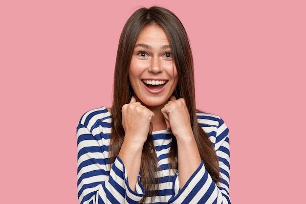 長い髪の楽しい若いそばかすのある女性の水平方向のショットは、広く笑顔