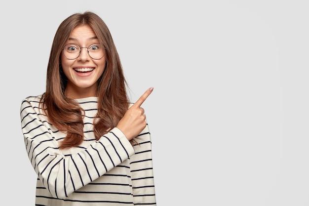 Горизонтальный снимок радостной молодой женщины в очках, позирующей у белой стены