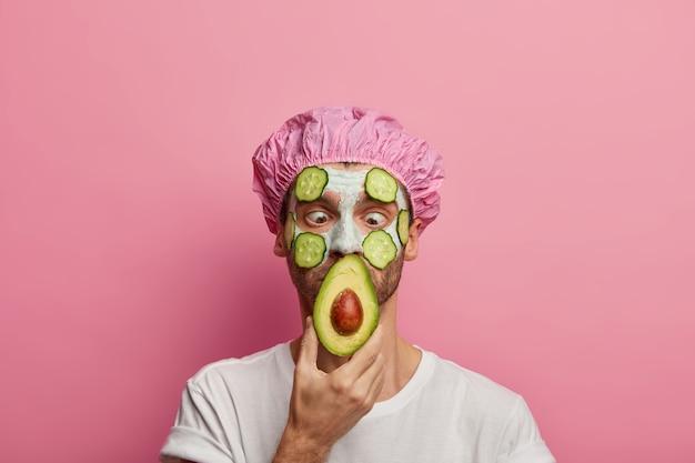 Горизонтальный снимок: мужчина смотрит на аковадо с заторможенными глазами, носит шапочку для ванны и наносит косметическую маску для лица.