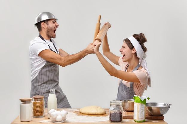 Горизонтальный снимок мужчин и женщин-противников, участвующих в кулинарном испытании, сражающихся деревянными скалками, кулинарной битвы, работы в пекарне, замешивания теста, позирования на кухне у белой стены