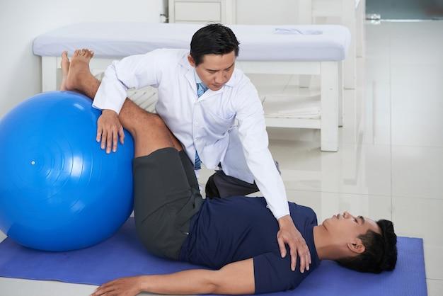 남성 환자가 재활을 위해 공을 사용하여 매트에서 운동을 하도록 돕는 현대 아시아 물리치료사의 수평 샷