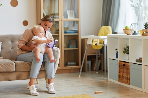 Горизонтальный снимок современной кавказской женщины в повседневной одежде, сидящей на диване со своим ребенком на коленях и играющей с игрушкой
