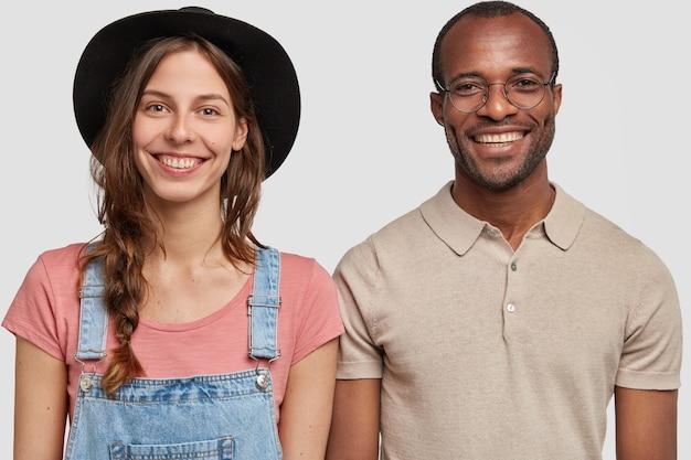 Горизонтальный снимок многонациональной женщины и мужчины, стоящих вместе у белой стены, широко улыбаясь, изолированные