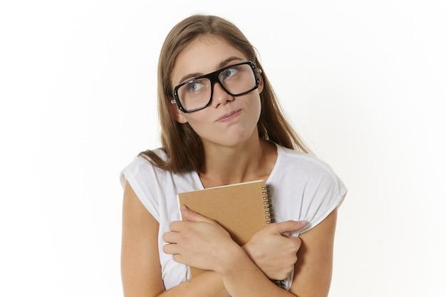 Горизонтальный снимок таинственной красивой молодой женщины в очках, которая смотрит в сторону и обнимает тетрадь или дневник, пытается скрыть что-то интересное, что она записала, не хочет делиться своим секретом