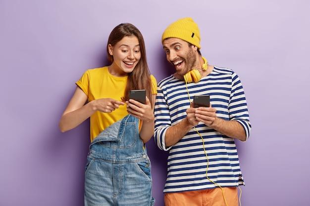 Горизонтальный снимок оптимистичной радостной пары, болтающей с подписчиками из веб-блога, радостно глядя на смартфон