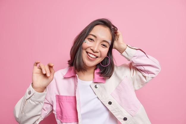 낙관적 평온한 아시아 여자의 가로 샷 진심으로 분홍색 벽에 고립 된 좋은 분위기에 유행 재킷을 입고 머리 미소를 기울입니다. 행복한 감정과 감정 개념