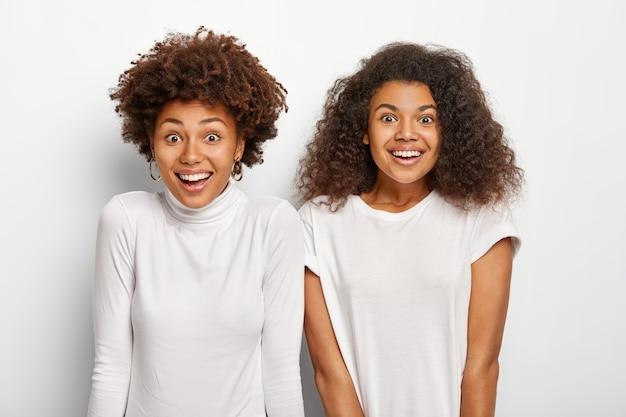 기뻐하는 여성의 가로 샷은 넓게 웃고, 활기차고 낙관적이며, 쾌활하게 이야기하고, 흰색 터틀넥과 티셔츠를 입습니다.