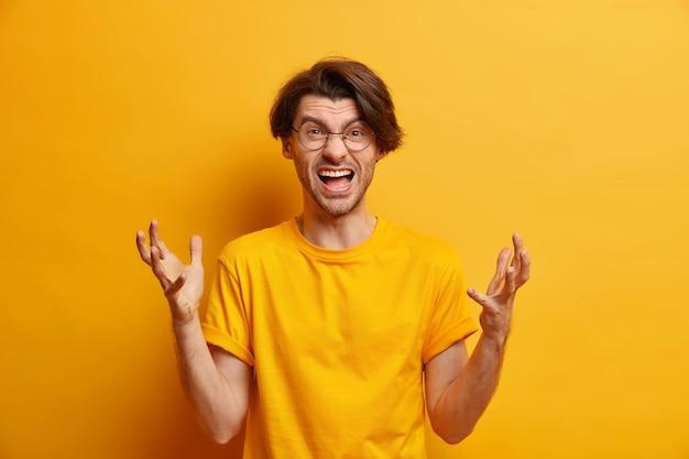 화난 유럽 남자의 가로 샷은 분노에서 적극적으로 외치며 좌절 한 표정으로 외친다. 캐주얼 한 노란색 티셔츠를 입고 부정적인 감정을 표현한다. 분노한 남자 비명