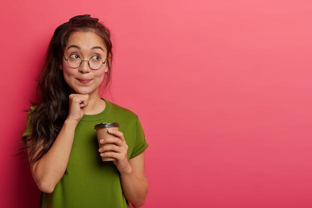 物思いにふけるアジアの女子高生が休暇を夢見て、あごの下で拳を握り、持ち帰り用のコーヒーを飲み、休憩を楽しみ、バラ色の壁に向かって屋内に立ち、眼鏡とtシャツを着ています。