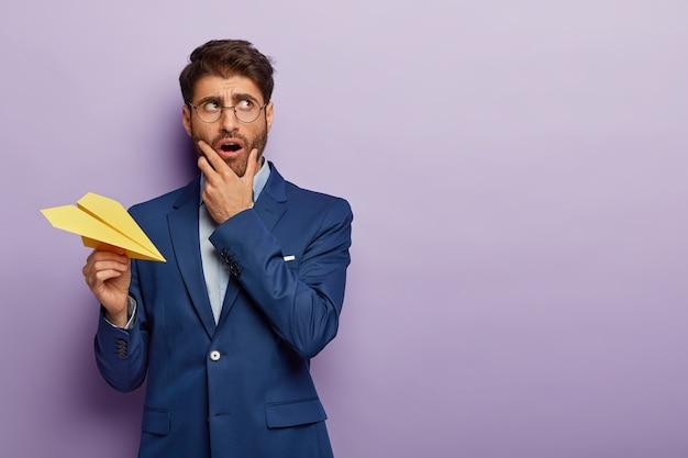 オフィスで上品なスーツでポーズをとって物思いにふけるビジネスマンの水平方向のショット