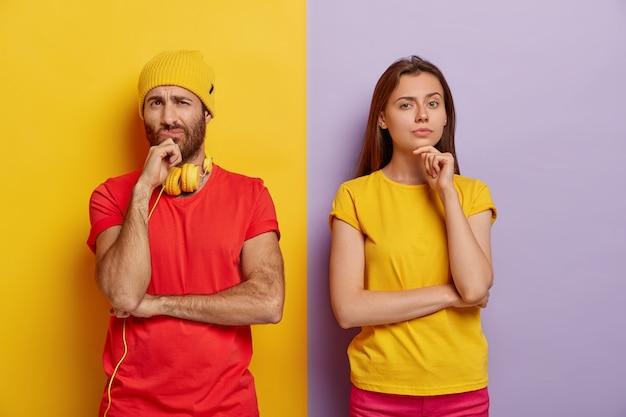 Горизонтальный снимок: задумчивая пара миллениалов держится за подбородки и смотрит с неудовольствием, носит яркую повседневную одежду, стоит вместе