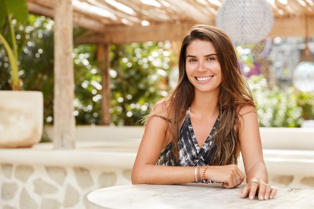 Горизонтальный снимок симпатичной брюнетки с веселым выражением лица сидит в кафе на террасе, с широкой улыбкой ждет заказа, проводит летние каникулы в экзотической стране. расслабленная рада женщина