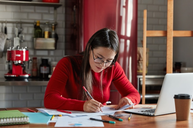 Горизонтальный снимок симпатичной деловой женщины, которая работает с бумагами дома, готовит отчет, заполняет информацию, сидит перед открытым ноутбуком на кухне.