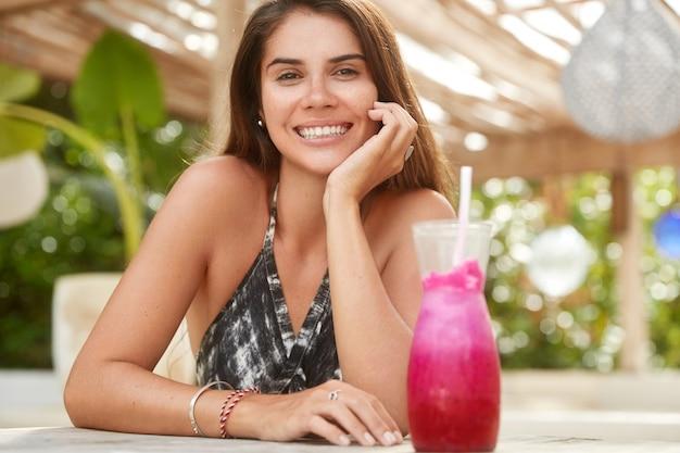 Горизонтальный снимок довольной очаровательной женщины с приятной улыбкой, проводит время отдыха, сидит в летнем кафе, встречается с другом.