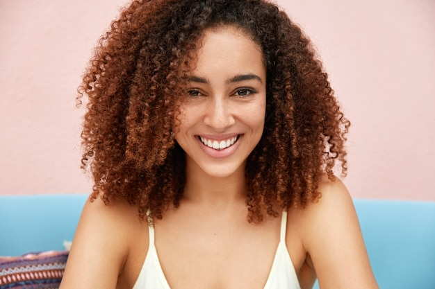 Горизонтальный снимок довольной привлекательной молодой девушки-модели с вьющимися темными волосами, приятной улыбкой на лице