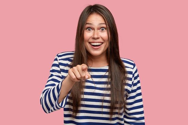 喜んでいるブルネットの女性の水平方向のショットは幸せな表情を持って、人差し指でカメラを直接指しています