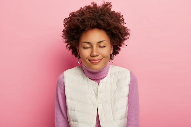 기쁘게 여자의 가로 샷은 곱슬 헤어 스타일, 눈을 감고, 차분한 표정을 가지고 있으며, 둥근 귀걸이와 캐주얼을 착용하고 분홍색 배경에 포즈를 취합니다.