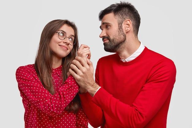 喜んでいる女性の水平方向のショットは、白い背景の上に隔離された、懇願するような表情と彼女の手を握り、赤い服を着て、楽しい話をしている夫を見ています。人
