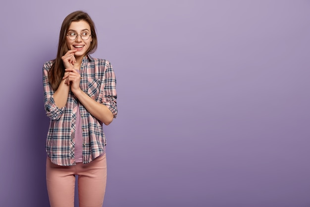 ヨーロッパの外観を持つ満足している女性の水平方向のショットは、顔に優しい笑顔を持って、目をそらし、光学眼鏡をかけています