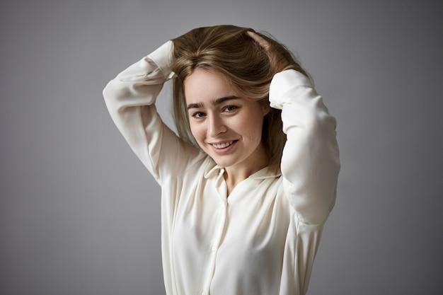 카메라에 즐겁게 웃고, 그녀의 긴 머리를 만지고, 새로운 헤어 스타일에 기뻐하는 우아한 흰 블라우스를 입고 긍정적 인 쾌활한 젊은 여자의 가로 샷. 사람, 패션 및 스타일 개념