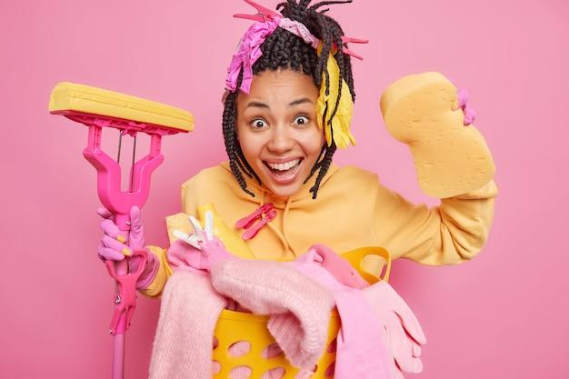Горизонтальный снимок позитивной темнокожей домохозяйки с косами держит швабру
