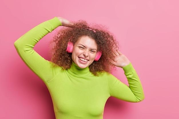 Горизонтальный снимок позитивной европейской женщины с вьющимися волосами, поднимающей руки, наклонившей голову, одетой в повседневную зеленую водолазку, слушает звуковую дорожку в наушниках, изолированных на розовой стене. стиль жизни