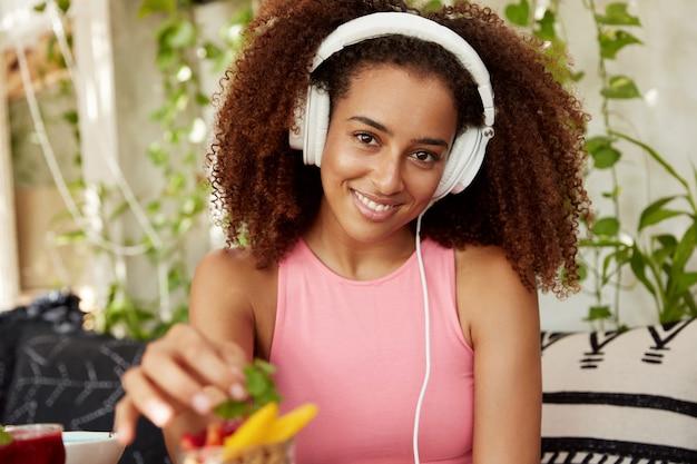 Горизонтальный снимок позитивной женщины, которая слушает новую музыку в современных наушниках, ожидает друга в кафе, ест фруктовый десерт, хорошо отдыхает. афро-американский студент отдыхает после лекций