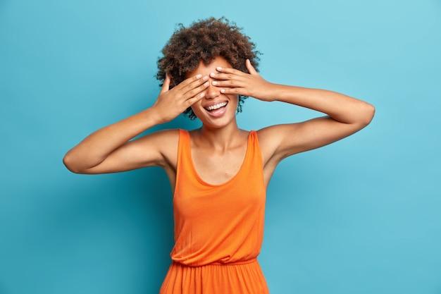 Горизонтальный снимок позитивной женщины с афро-волосами прикрывает глаза руками, улыбается и радостно ждет, когда удивленная носит летнее платье, изолированное от синей стены