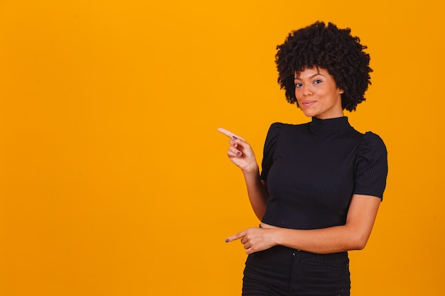 멀리 앞 손가락으로 예쁜 젊은 즐거운 아프리카 계 미국인 여성 포인트의 가로 샷 노란색 배경 위에 절연 빈 벽에 복사 공간을 나타냅니다. 이것 좀 봐. 민족성 개념