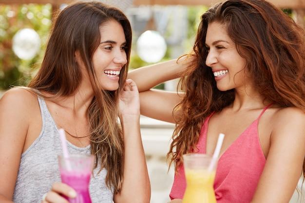 Горизонтальный снимок симпатичных брюнеток, которые весело смотрят друг на друга, наслаждаются летними напитками, приятно беседуют.