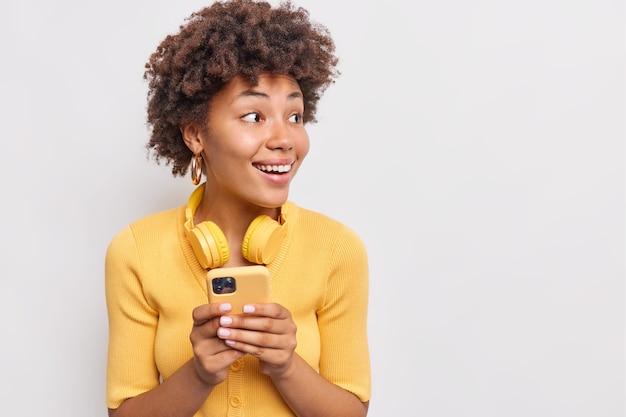 꽤 곱슬머리 여성의 가로 사진은 흰 벽에 캐주얼하게 격리된 옷을 입고 소셜 네트워크에서 온라인으로 휴대전화 다운로드 새 응용 프로그램 채팅을 사용하여 관심을 가지고 시선을 돌립니다.