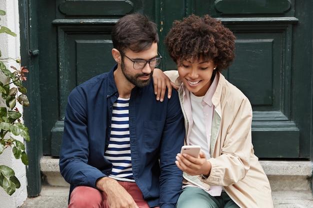 Горизонтальный снимок довольно темнокожей девушки показывает ее фотографии на мобильный телефон лучшему другу