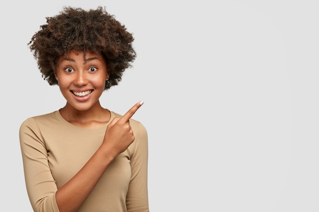 아프로 헤어 스타일로 꽤 어두운 피부를 가진 여성의 가로 샷, 넓은 미소, 하얀 이빨, 친구에게 좋은 것을 보여주고 오른쪽 상단 모서리를 가리키며 벽에 서 있습니다.