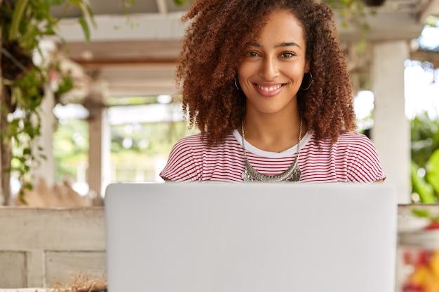 Горизонтальный снимок симпатичной женщины-фрилансера, сидящей перед открытым портативным компьютером