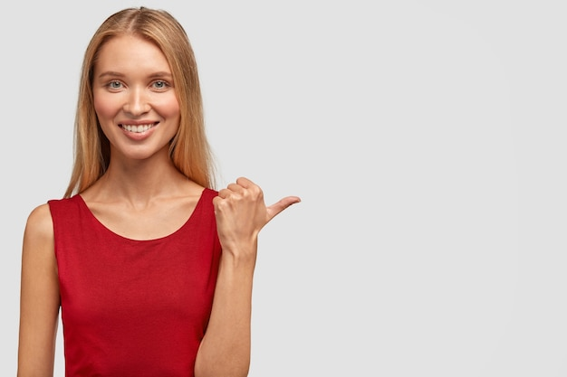 かなり幸せなスリムな女性の水平方向のショットは、優しい笑顔、魅力的な外観、親指を脇に置いたポイント、赤いtシャツを着ています