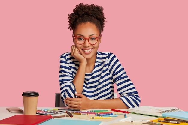 평상복을 입은 예쁜 전문 디자이너의 가로 샷, 턱 밑에 손을 대고, 완성 된 작업으로 만족감을 느끼고, 좋아하는 취미 그림을 즐기고, 분홍색 벽 위에 모델. 창의력