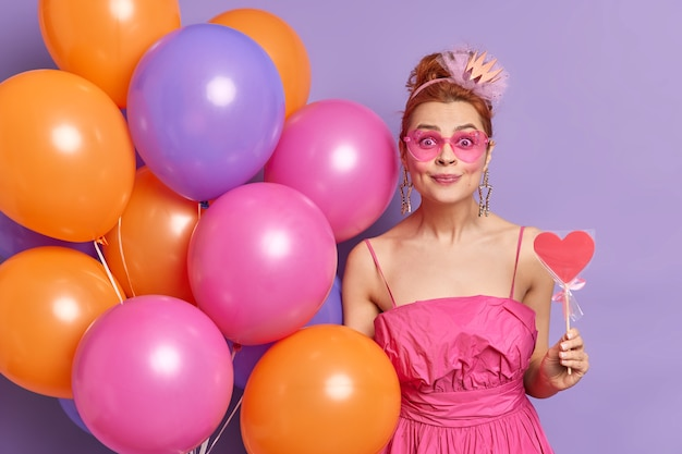 Горизонтальный снимок красивой рыжей девушки-модели, радостно смотрящей в камеру, принимает поздравления со счастливым выражением лица, держит конфету в форме сердца