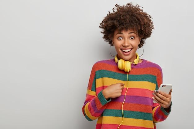 Горизонтальный снимок красивой женщины, указывающей на себя, счастливой, что ее выбрали для продвижения по службе, держит современный мобильный телефон, желтые наушники на шее