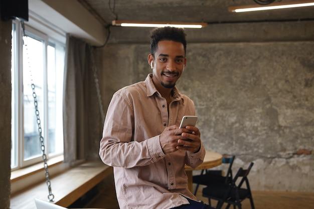 ベージュのシャツを着てカフェのインテリアにポーズをとって、スマートフォンを上げたままにして、カーミングな笑顔でカメラを見ているかなり若い暗い肌の男の水平方向のショット