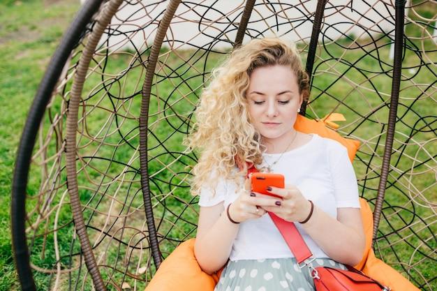 Горизонтальный снимок довольно молодая самка лежит в подвесном кресле в саду, использует смартфон