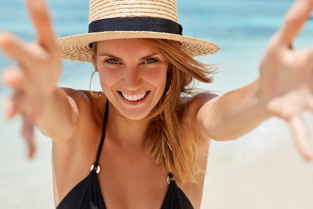 Горизонтальный снимок симпатичной молодой туристки, которая развлекается на берегу моря, протягивает руки, собираясь кого-то обнять, выражает счастье, забывает обо всех проблемах в райском месте для прекрасного отдыха