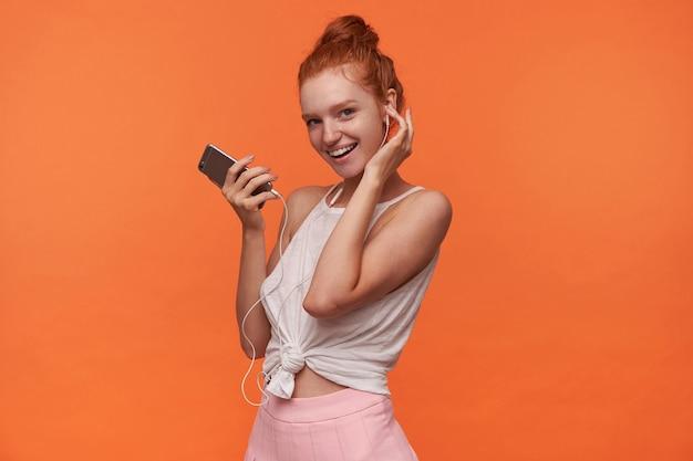カジュアルな服を着て、カーミングな笑顔でカメラを見て、ヘッドフォンで音楽を聴きながらスマートフォンを手に持って、結び目の髪を持つかなり若い赤毛の女性の水平方向のショット