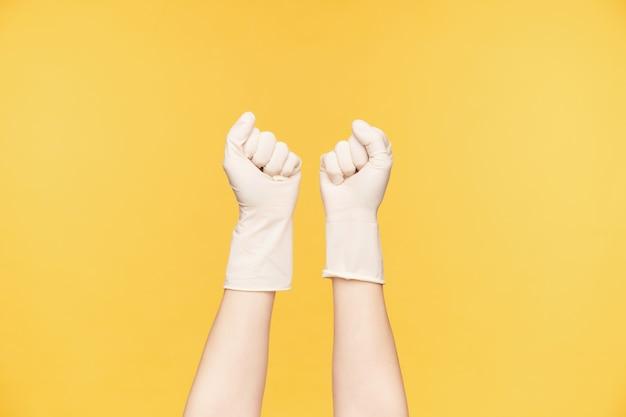 오렌지 배경 위에 포즈를 취하는 동안 주먹을 떨림 고무 장갑에 제기 젊은 여자의 손의 수평 샷. 청소 및 집 관리 개념