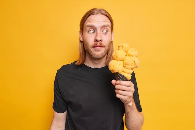 赤毛のひげを生やした男の水平方向のショットは、おいしい黄色いアイスクリームがおいしい冷凍デザートを食べて飢えていることにショックを受けているように見え、屋内にカジュアルな黒い t シャツ スタンドを着ています。夏季休業日